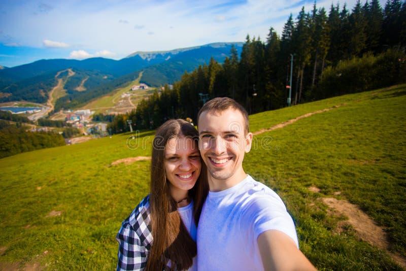 Jeunes couples augmentant prenant le selfie avec le téléphone intelligent Jeune homme heureux et femme prenant l'autoportrait ave photo libre de droits
