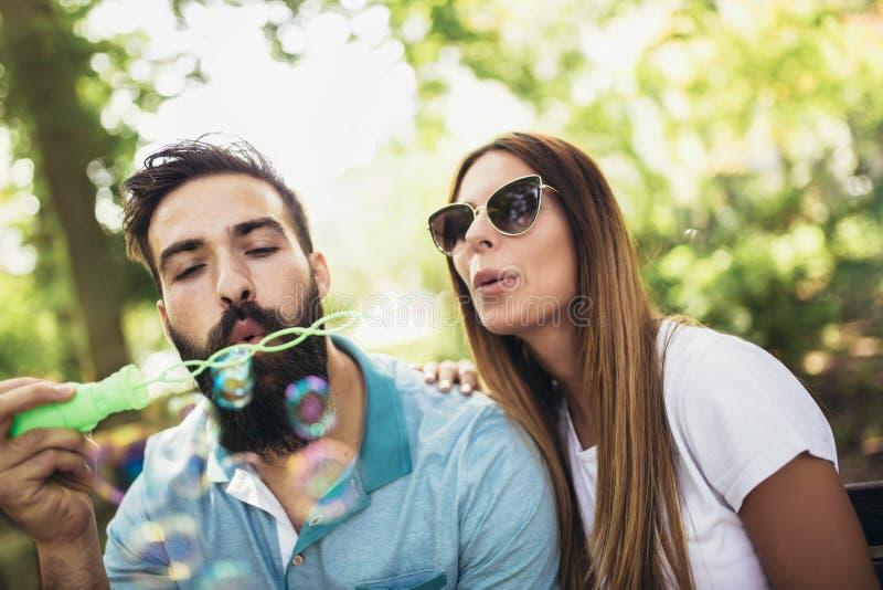 Jeunes couples avec du charme se reposant sur le banc image stock
