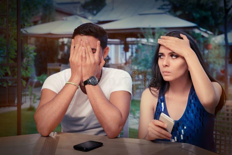 Jeunes couples ayant des problèmes avec leurs téléphones intelligents photographie stock libre de droits