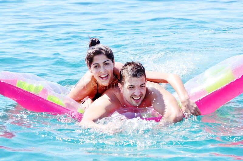 Jeunes couples ayant l'amusement sur le matelas de natation en mer images stock