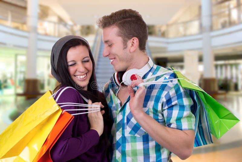 Jeunes couples ayant l'amusement tout en faisant des emplettes dans un centre commercial photographie stock libre de droits