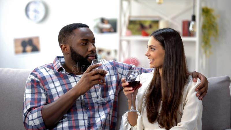 Jeunes couples ayant la date romantique avec la boisson de vin à la maison, unité photographie stock