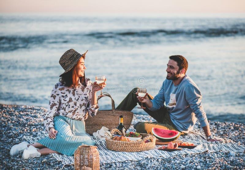 Jeunes couples ayant le pique-nique au bord de la mer avec du vin photos libres de droits