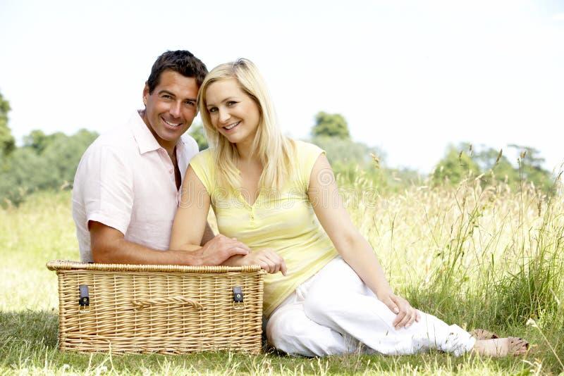 Jeunes couples ayant le pique-nique dans la campagne photographie stock libre de droits