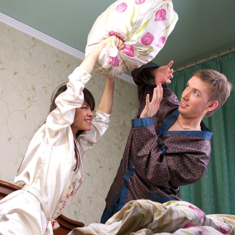 Jeunes couples ayant un combat d'oreiller photos libres de droits