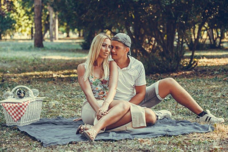 Jeunes couples ayant un pique-nique dans le parc un jour ensoleill? photos stock