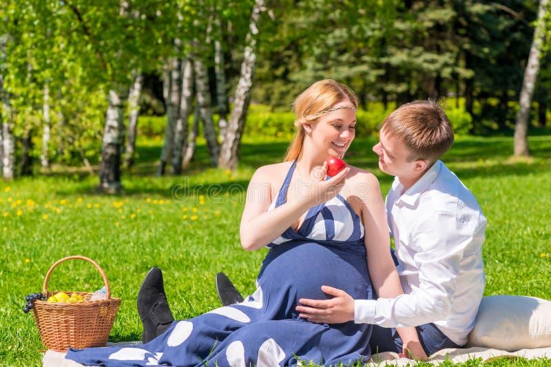 Jeunes couples ayant un pique-nique dans un parc de ville photos stock