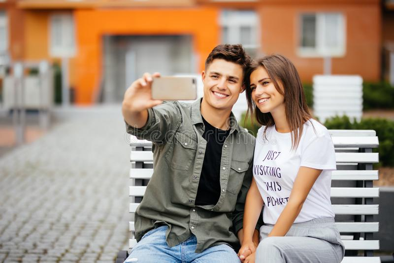 Jeunes couples beaux se reposant sur le banc au centre de la ville et prenant un selfie avec un comprimé Concept de mode de vie image libre de droits