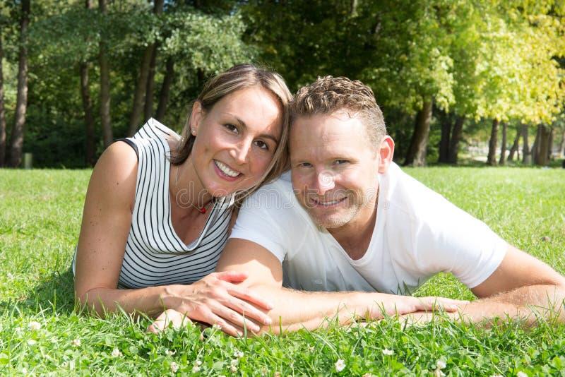 jeunes couples blonds menteur de sourire étreignant l'amour dehors photos stock