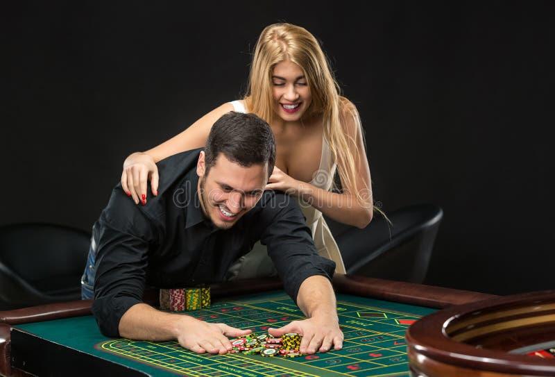 Jeunes couples célébrant la victoire à la table de roulette dans le casino photos libres de droits