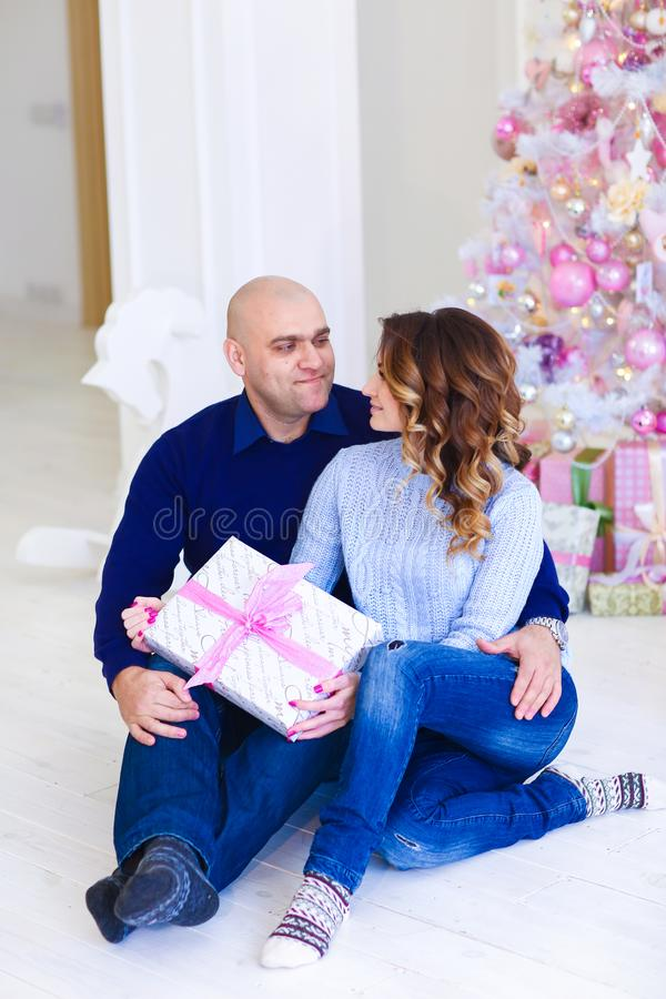 Jeunes couples caucasiens heureux se reposant près de l'arbre de sapin rose décoré avec le présent photos stock