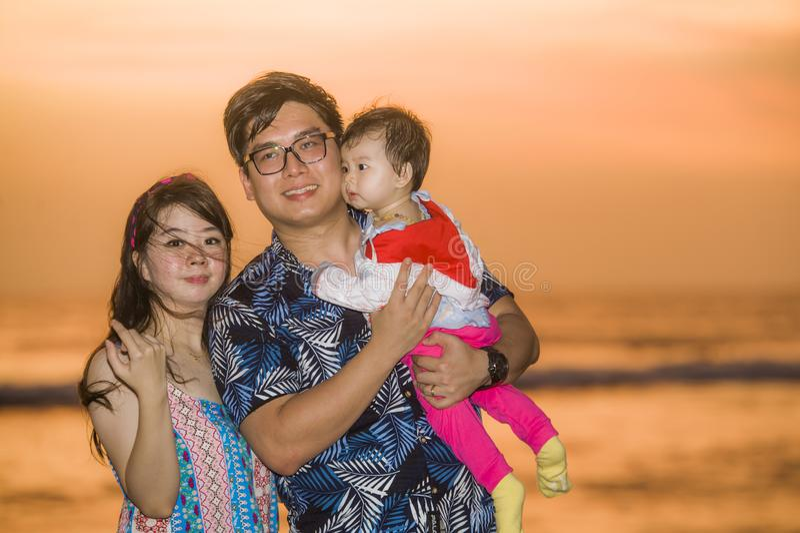 Jeunes couples chinois asiatiques heureux et beaux tenant la fille de bébé marchant sur la plage de coucher du soleil appréciant  photographie stock libre de droits