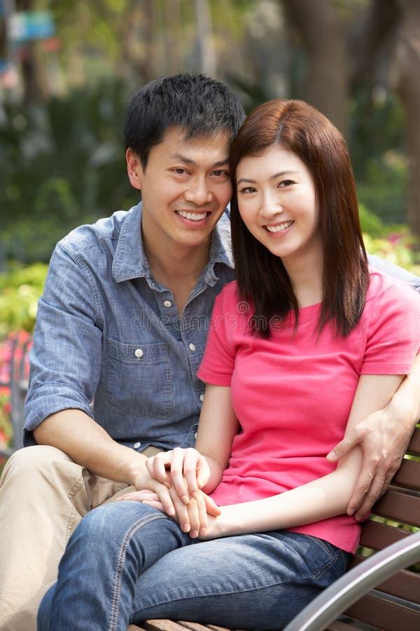 Jeunes couples chinois détendant sur le banc de stationnement image stock