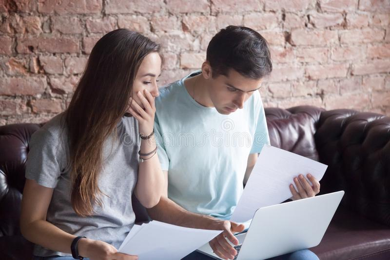 Jeunes couples choqués regardant les documents et l'ordinateur portable photos stock