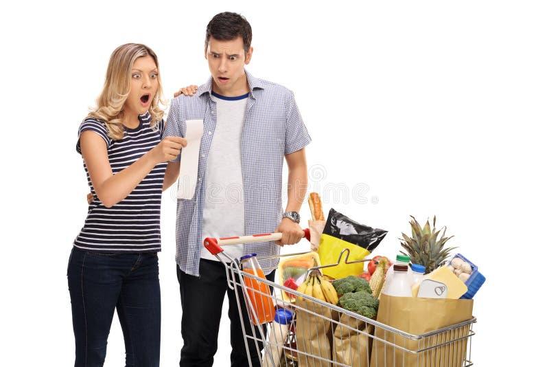 Jeunes couples choqués regardant une facture d'achats photos stock