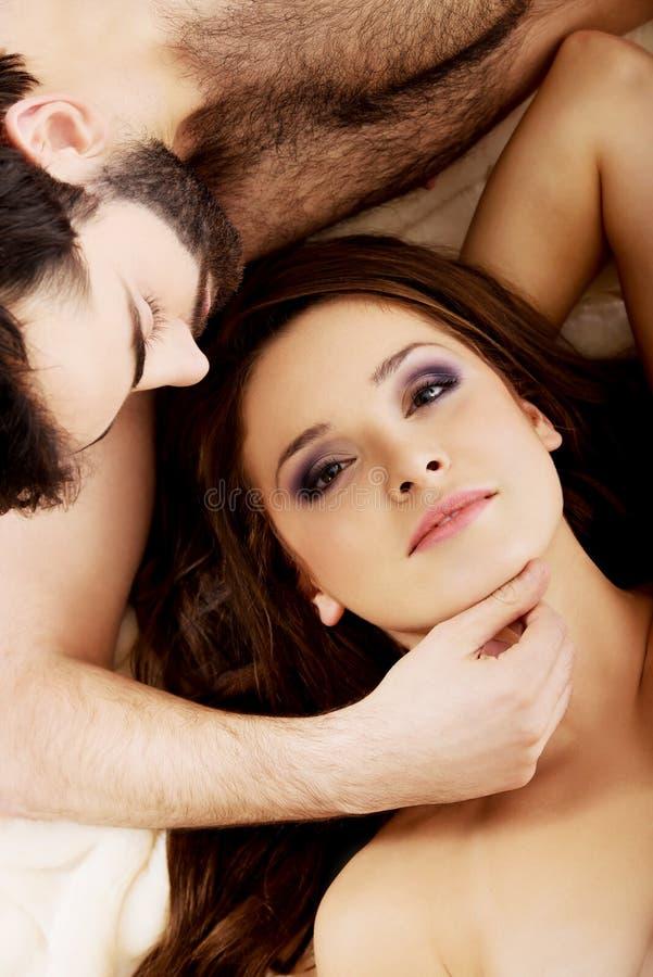 Jeunes couples décontractés se situant dans le lit photographie stock libre de droits