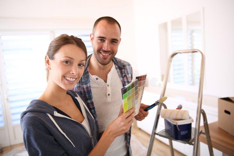 Jeunes couples décorant leur nouvel appartement images stock