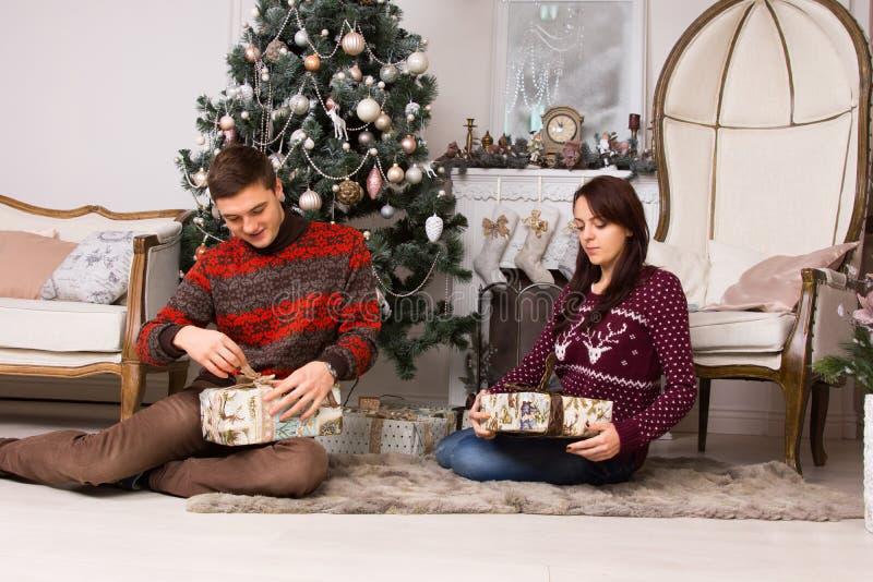Jeunes couples déroulant leurs cadeaux de Noël photos stock