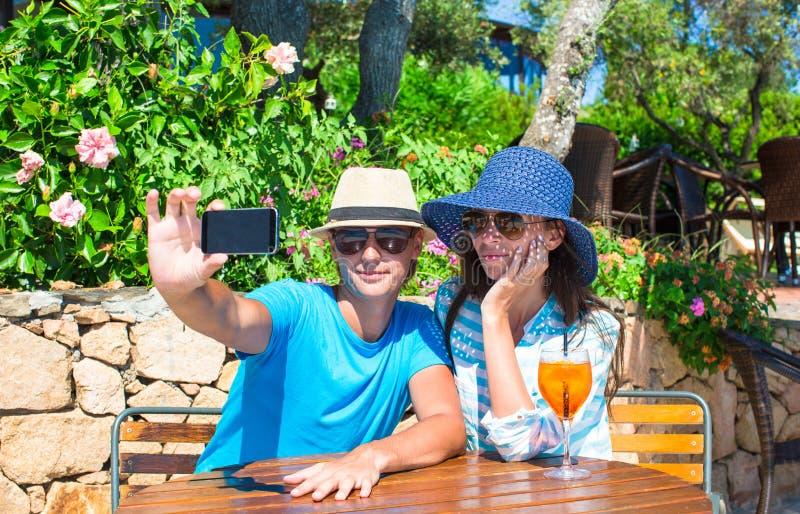 Jeunes couples détendant en café extérieur image stock