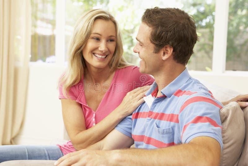 Jeunes couples détendant sur le sofa à la maison photo stock