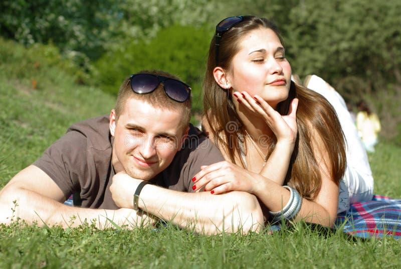 Jeunes couples détendant sur le vert photographie stock libre de droits