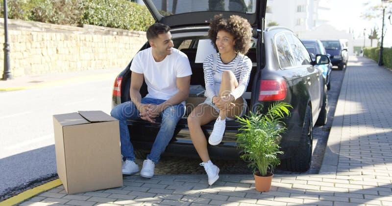 Jeunes couples détendant tout en déplaçant la maison image libre de droits