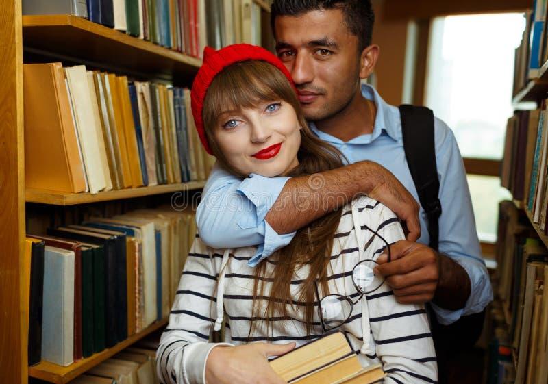 Jeunes couples d'étudiant choisissant des livres dans la bibliothèque image libre de droits