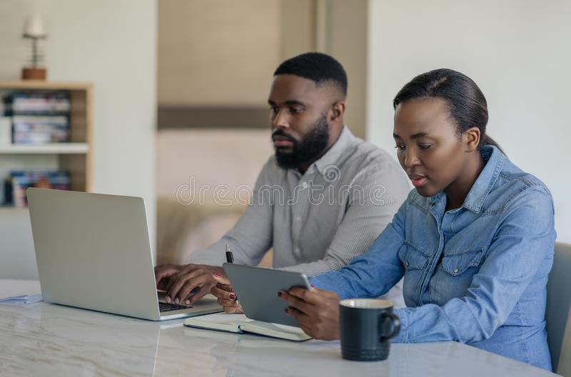 Jeunes couples d'Afro-américain faisant des opérations bancaires en ligne ensemble à la maison images libres de droits