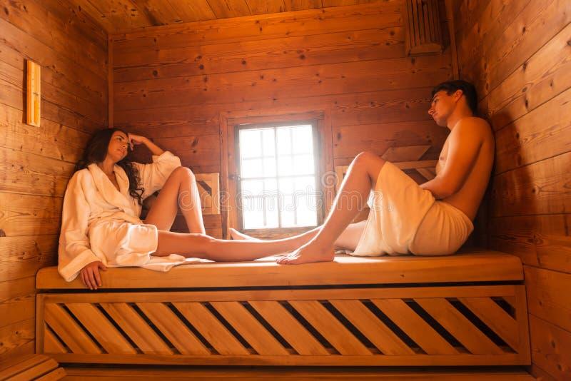 Jeunes couples d'amour détendant dans le sauna photos libres de droits