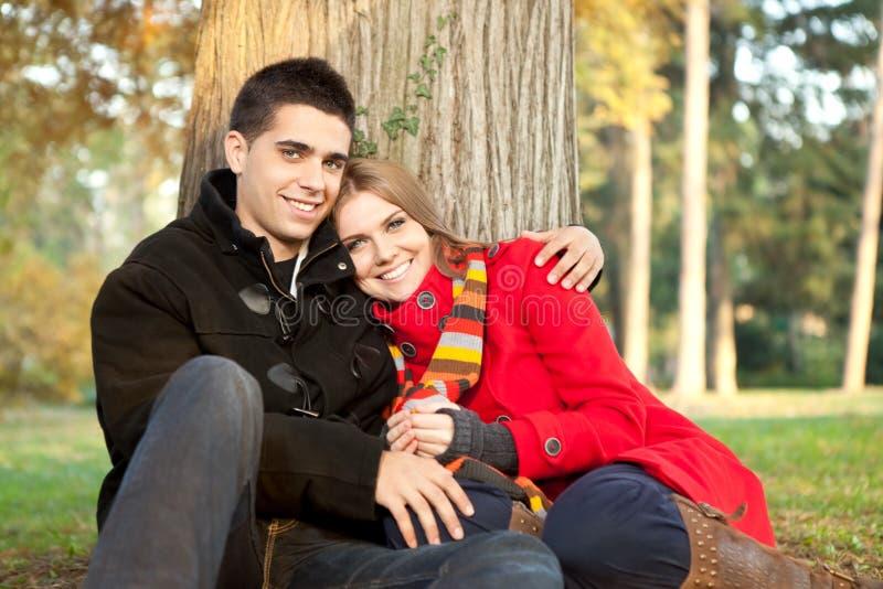 Jeunes couples d'amour détendant en stationnement image stock