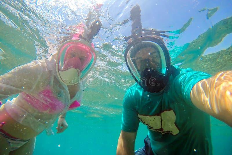 Jeunes couples dans de pleins masques protecteurs pour le selfie de fabrication naviguant au schnorchel sous l'eau image libre de droits