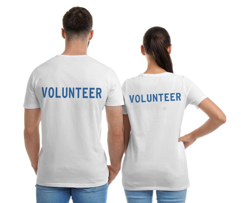 Jeunes couples dans des T-shirts sur le fond blanc image stock