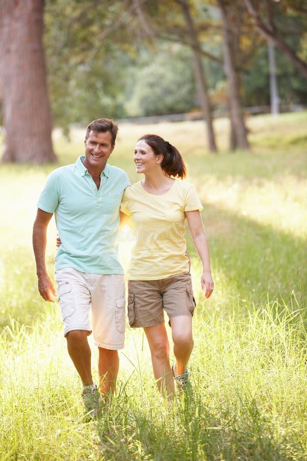 Jeunes couples dans des vêtements de marche marchant en stationnement images libres de droits