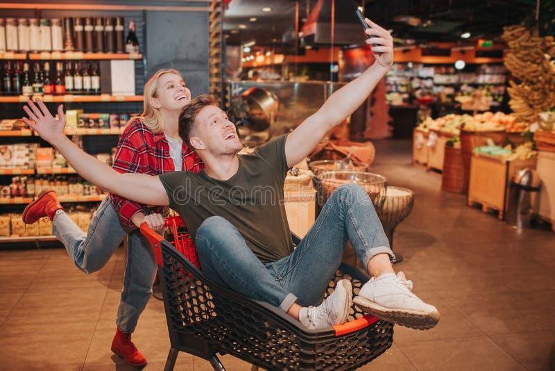 Jeunes couples dans l'épicerie L'homme espiègle s'asseyent dans le chariot et la vague avec des mains Support blond heureux de fe photo stock