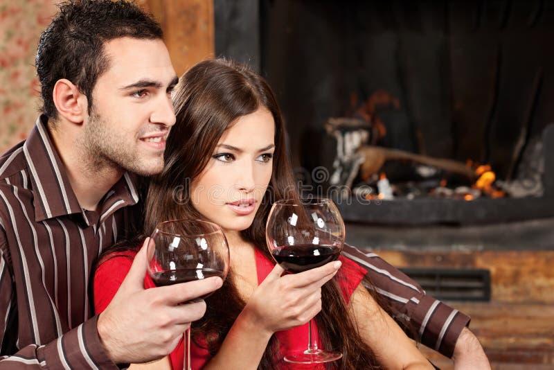 Couples appréciant le vin près de la cheminée photographie stock
