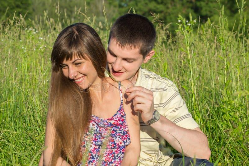 Jeunes couples dans l'amour avec des wildflowers sur l'herbe images libres de droits