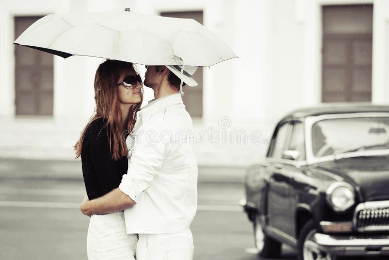 Jeunes couples dans l'amour avec le parapluie photo stock