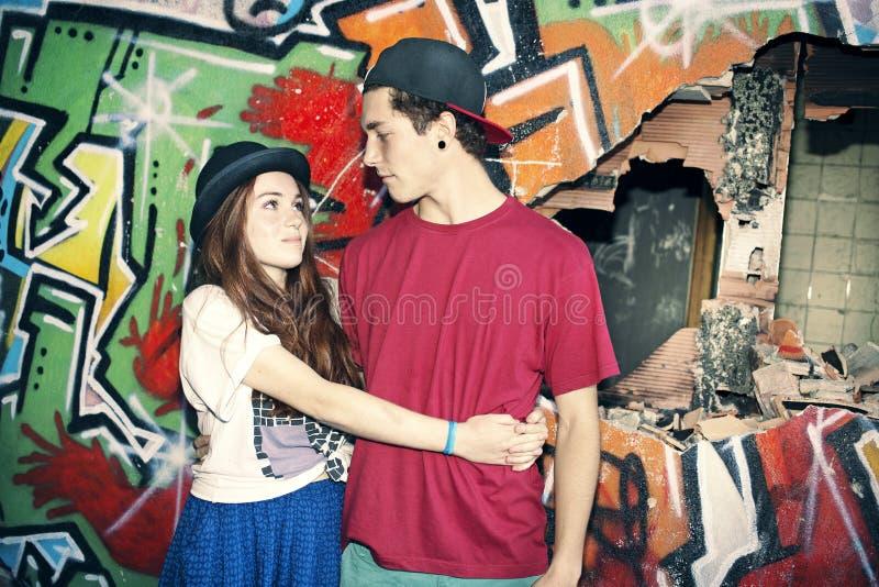 Jeunes couples dans l'amour dans un endroit urbain avec le graffiti image libre de droits