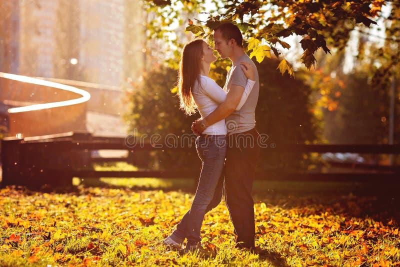 Jeunes couples dans l'amour, embrassant sur le coucher du soleil en parc photo libre de droits