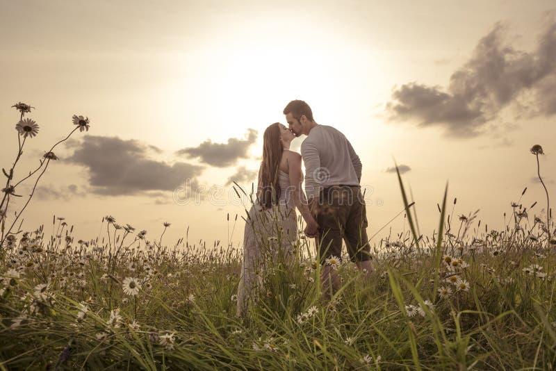 Jeunes couples dans l'amour extérieur au coucher du soleil image libre de droits