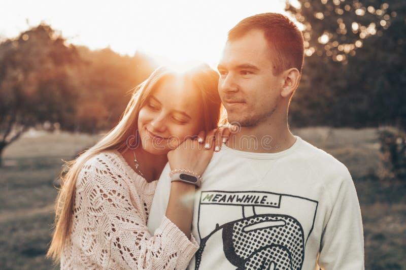 Jeunes couples dans l'amour extérieur Ils sont souriants et regardants l'un l'autre la lumière du soleil de soirée, étreint et de photographie stock libre de droits