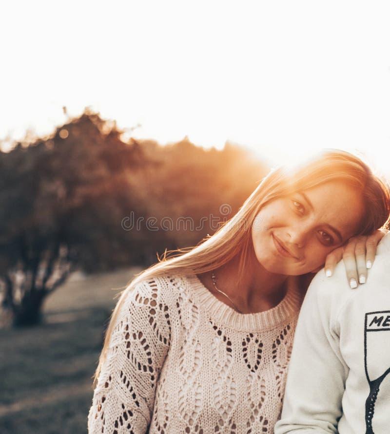 Jeunes couples dans l'amour extérieur Ils sont souriants et regardants l'un l'autre la lumière du soleil de soirée, étreint et de photographie stock