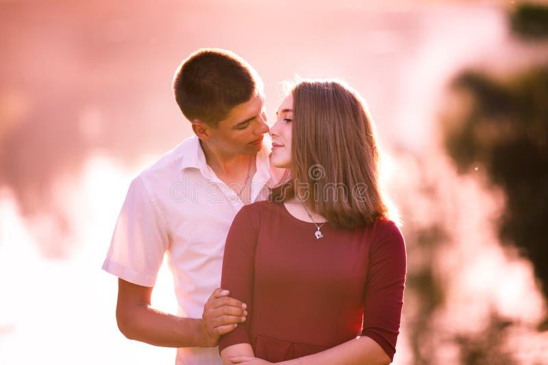 Jeunes couples dans l'amour se tenant et embrassant à la rivière photos stock