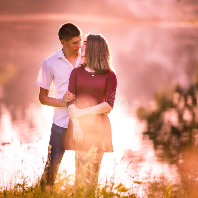 Jeunes couples dans l'amour se tenant et embrassant à la rivière photographie stock