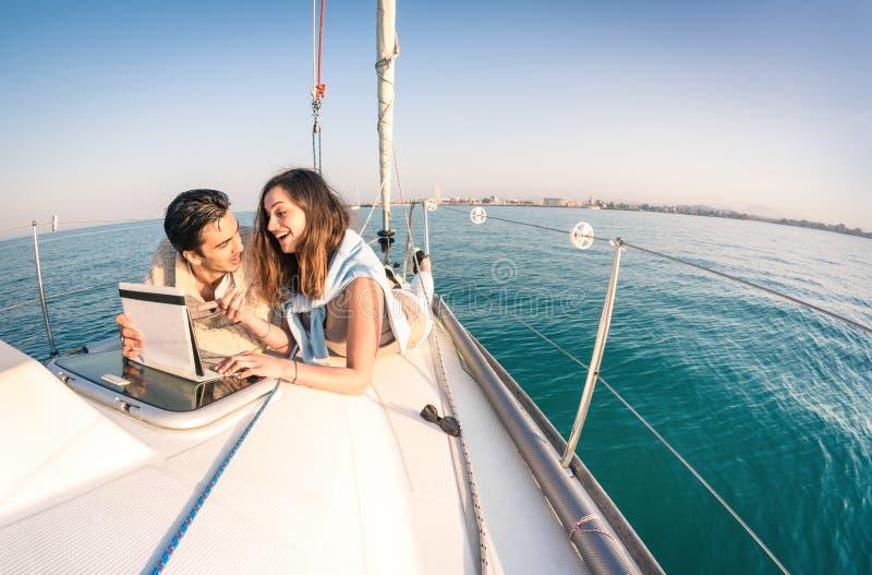 Jeunes couples dans l'amour sur le bateau à voile ayant l'amusement avec le comprimé photographie stock