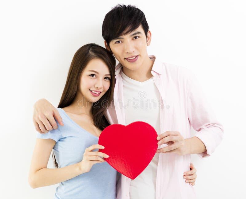 Jeunes couples dans l'amour tenant le coeur rouge photo libre de droits