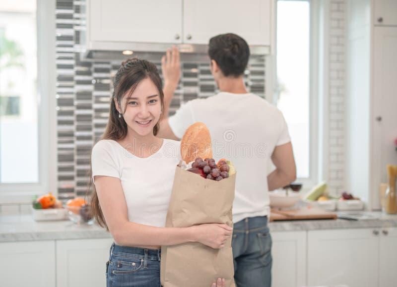 Jeunes couples dans la cuisine, femme avec un sac des achats d'épiceries image libre de droits