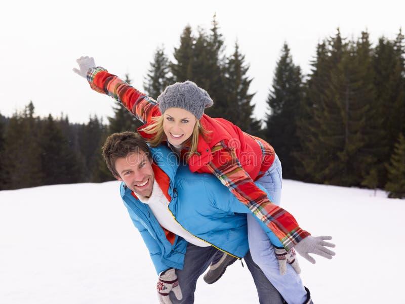 Jeunes couples dans la scène alpestre de neige photos stock
