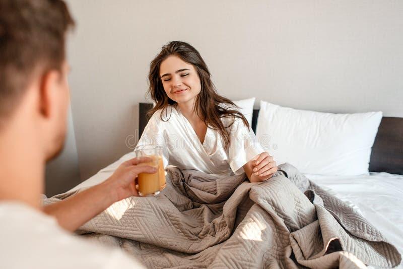 Jeunes couples dans le bâti La belle femme de sourire boit du jus pendant le matin, foyer sélectif image libre de droits