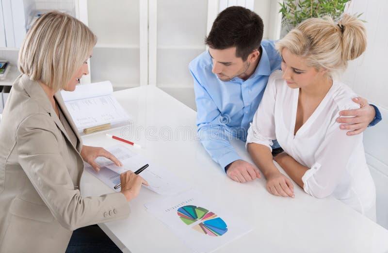 Jeunes couples dans une date avec un banquier ou un conseiller pour la retraite a images stock